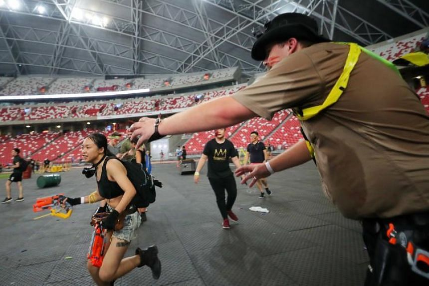 """A """"zombie"""" tries to catch a """"survivor"""" at Zedtown Asia: Battle for Singapore at the National Stadium on Oct 26, 2019."""