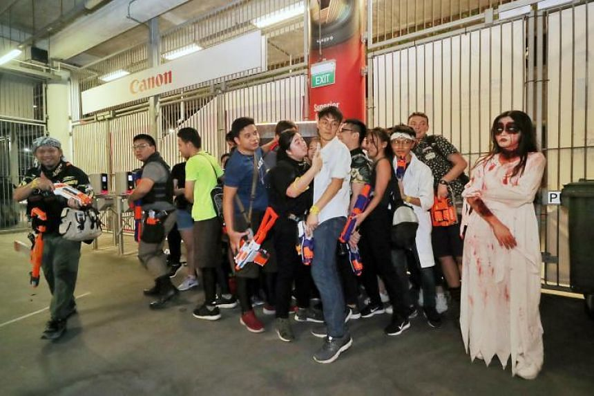 """""""Survivors"""" touching a safe zone device as a """"zombie"""" hangs around and waits for anyone who tries to run away at Zedtown Asia: Battle for Singapore at the National Stadium on Oct 26, 2019."""
