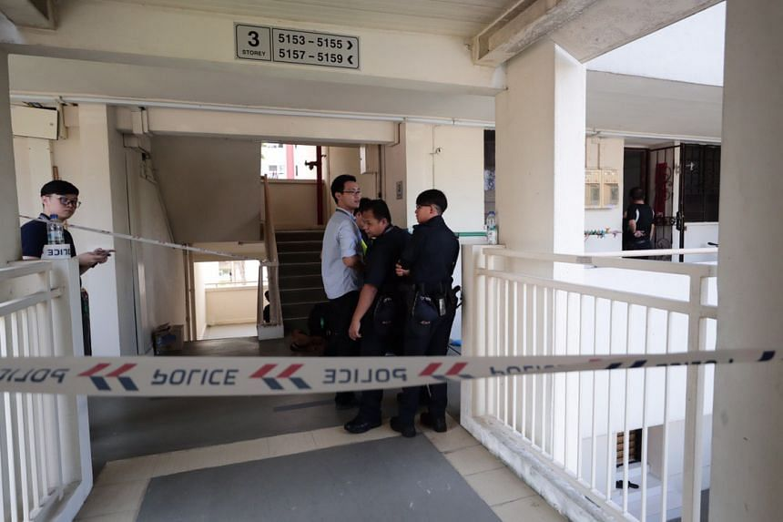 Police officers outside the victim's unit at Block 633 Ang Mo Kio Avenue 6.