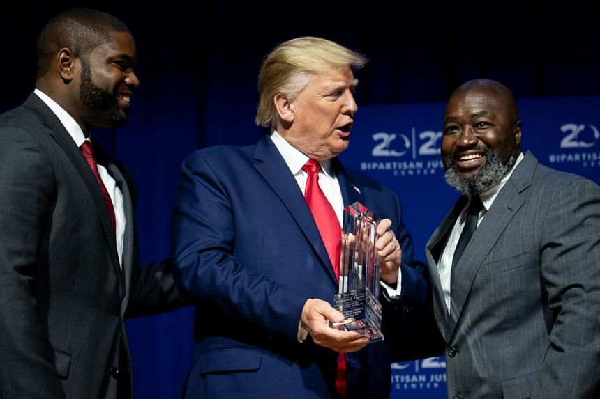 Trump is presented with an award by Byron Donalds (left) and Matthew Charles at Benedict College in Columbia, South Carolina.