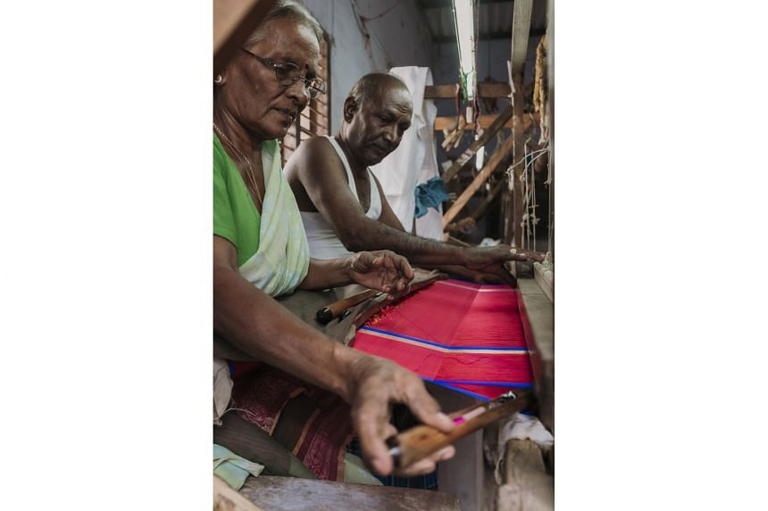 One weaver sends the shuttle across while another receives, repeating the process until the cloth is completed.