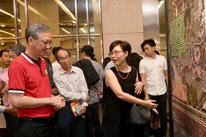 Guest of honour and Minister of State Sam Tan is guided by adjunct assistant professor at the NUS department of architecture, Dr Chen Yu, at an exhbition showing different aspects of Hokkien architecture, both in China and in Singapore.