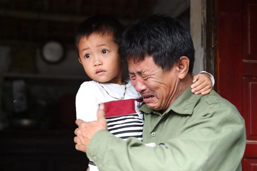 Le Minh Tuan, father of 30-year old Le Van Ha, who is feared to be among the 39 people found dead in a truck in Britain, cries while holding Ha's son outside their house in Vietnam, on Oct 27, 2019.