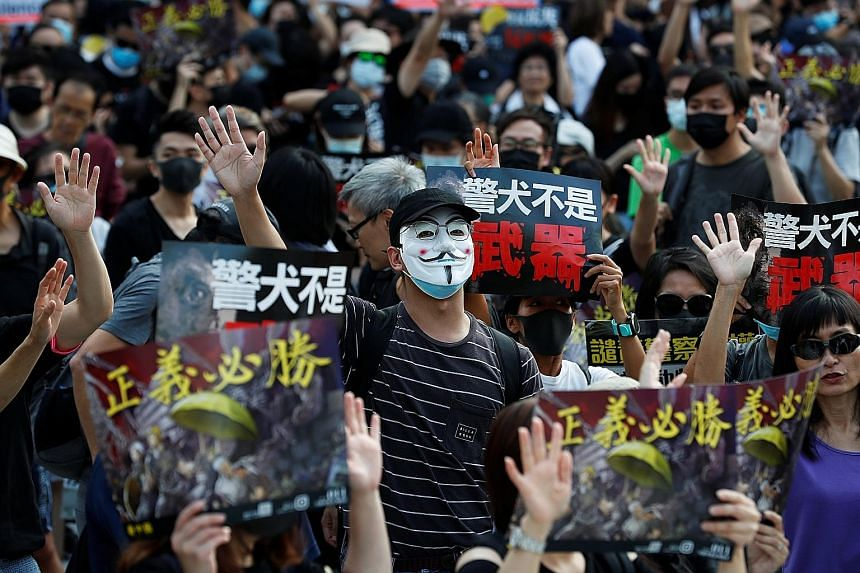 A demonstrator in a Guy Fawkes mask at a rally protesting against alleged police brutality in Hong Kong's Tsim Sha Tsui district yesterday. PHOTO: REUTERS