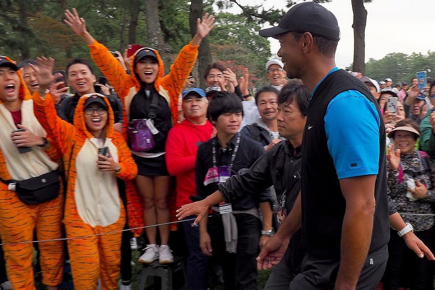 Fans wearing tiger costumes roaring for Tiger Woods in the third round of the Zozo Championship yesterday. He will match Sam Snead's 82 PGA titles with a win today.