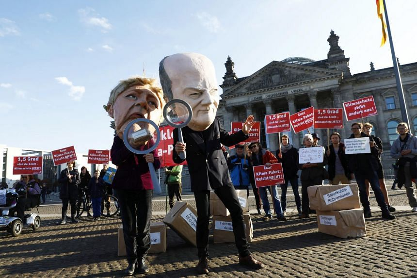 A photo taken on Oct 25 shows members of the NGO Campact protesting against the climate policies of the German government in front of the Reichstag building housing the German parliament in Berlin.