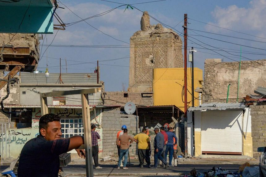 """The remains of the destroyed """"Al-Hadba"""" leaning minaret (centre) next to the Al-Nuri Mosque (unseen) in the former base of the ISIS group in northern Iraq, where Abu Bakr al-Baghdadi used to address followers before the group was chased out of the ar"""