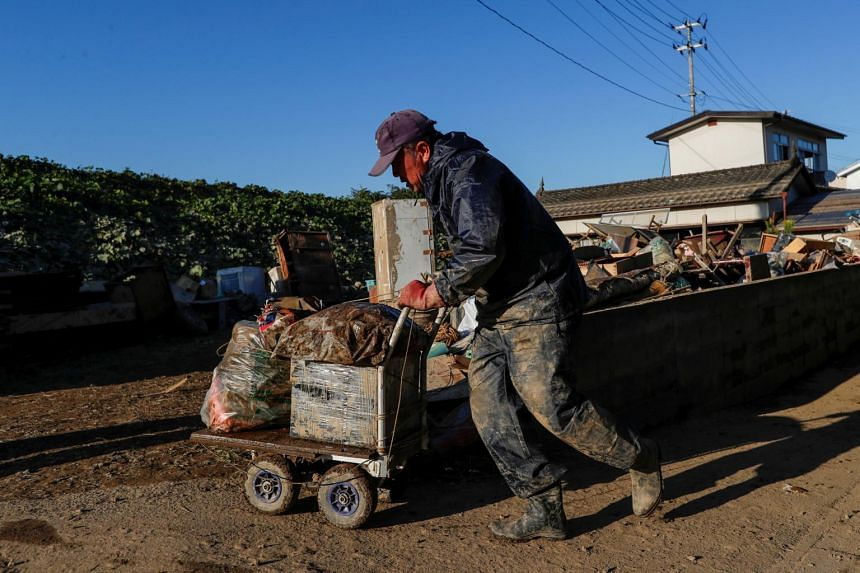 In a photo from Oct 16, 2019, a man clears debris in the aftermath of Typhoon Hagibis in Fukushima prefecture, Japan.