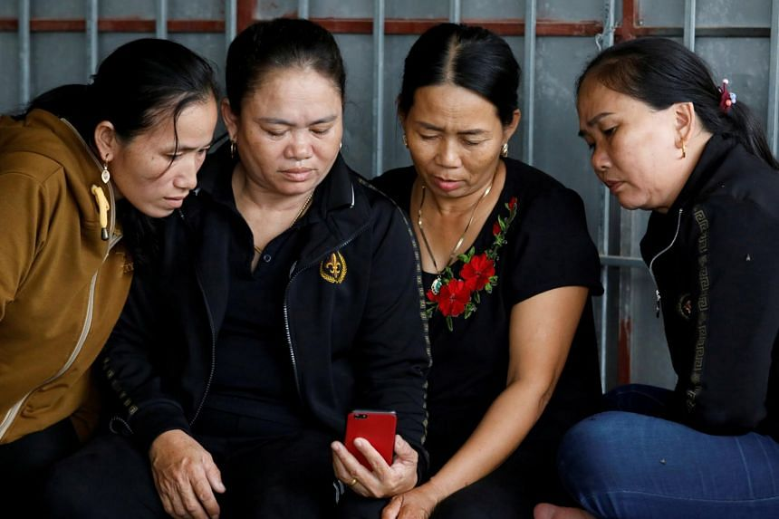 Relatives of Anna Bui Thi Nhung, a Vietnamese suspected to be among dead victims found in a lorry in Britain, reading news about her at her home in Nghe An province, Vietnam, on Oct 26, 2019.