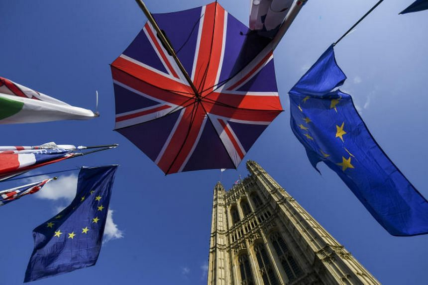 An umbrella featuring the design of the Union flag, also known as the Union Jack, stands near European Union (EU) flags outside the Houses of Parliament in London, on Oct 22, 2019.