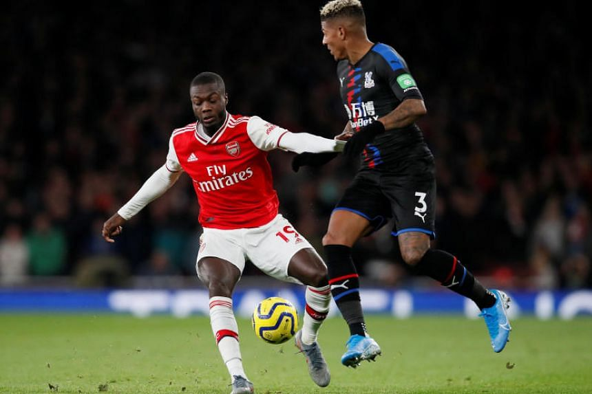 Arsenal's Nicolas Pepe (left) in action with Crystal Palace's Patrick van Aanholt during their English Premier League match at the Emirates Stadium in London on Oct 27, 2019.
