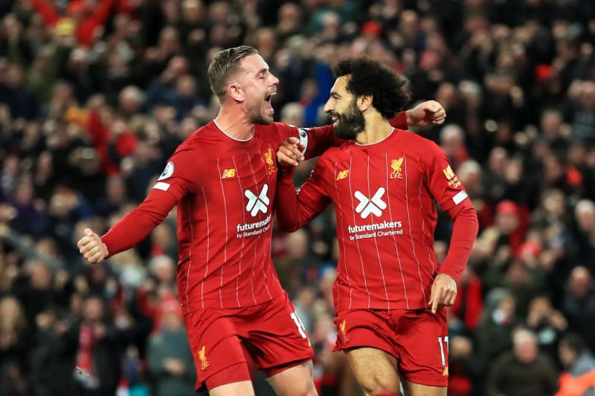Liverpool's Mohamed Salah (right) celebrates scoring his side's second goal with Jordan Henderson during the English Premier League soccer match between Liverpool and Tottenham Hotspur at Anfield stadium on Oct 27, 2019.