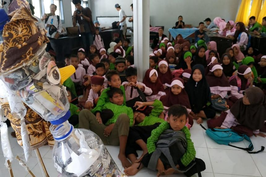 In a photo from Aug 16, 2019, students view puppets made out of plastic waste that are displayed in a primary school in Mataram on Lombok island, Indonesia.