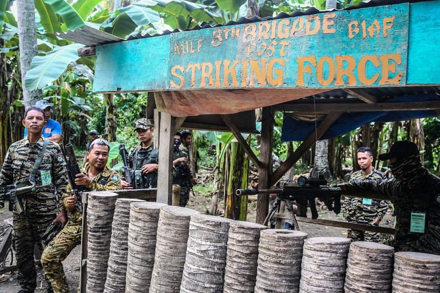 In a photo from Sept 7, 2019, Moro Islamic Liberation Front (MILF) rebels stand guard at the entry of Camp Darapanan on the southern Philippine island of Mindanao.