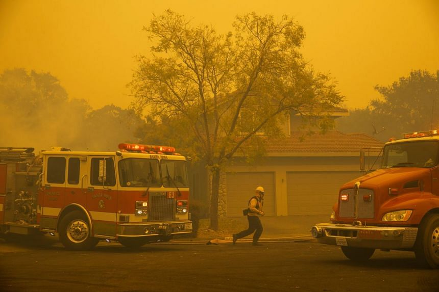 Firefighters battle hot spots and conduct structure protection in a Foothill subdivision neighbourhood in Windsor, California, on Oct 27, 2019.
