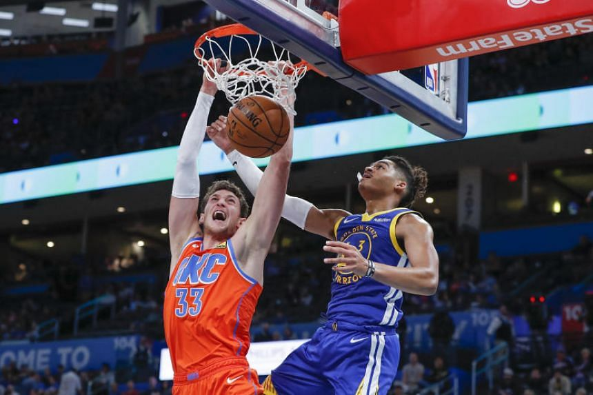 Oklahoma City Thunder's Mike Muscala dunks in front of Golden State Warriors' Jordan Poole during their NBA match at Chesapeake Energy Arena on Oct 27, 2019.