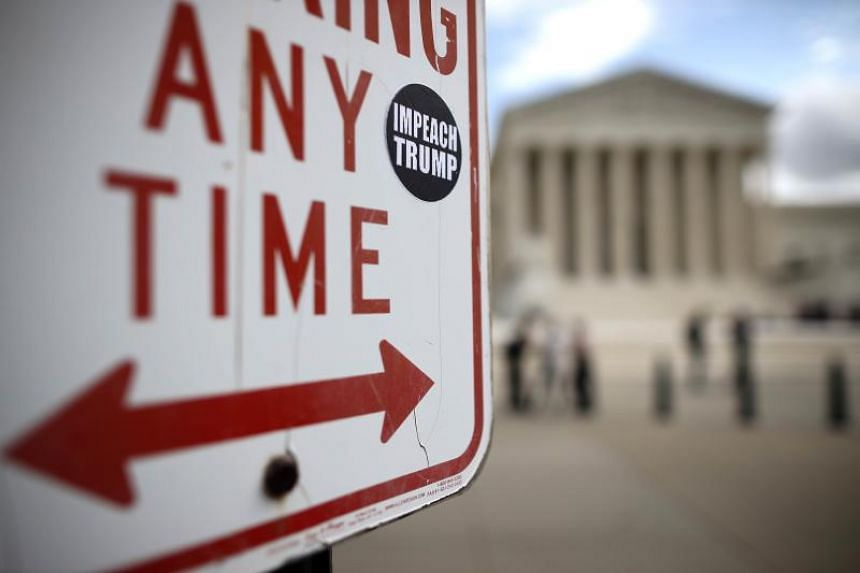 A photo taken on Oct 7 shows a sticker calling for the impeachment of US President Donald Trump adhered to a sign outside the US Supreme Court building.
