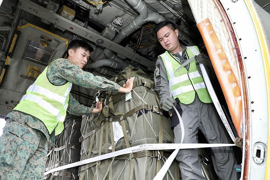 Corporal Markus Yuen Wei Chen (left) and Staff Sergeant Keith Ho Kee Hou doing an inspection of the supplies to be airdropped from a C-130 Hercules aircraft. The second frame of the exercise at the Shoalwater Bay Training Area runs from Oct 15 to nex