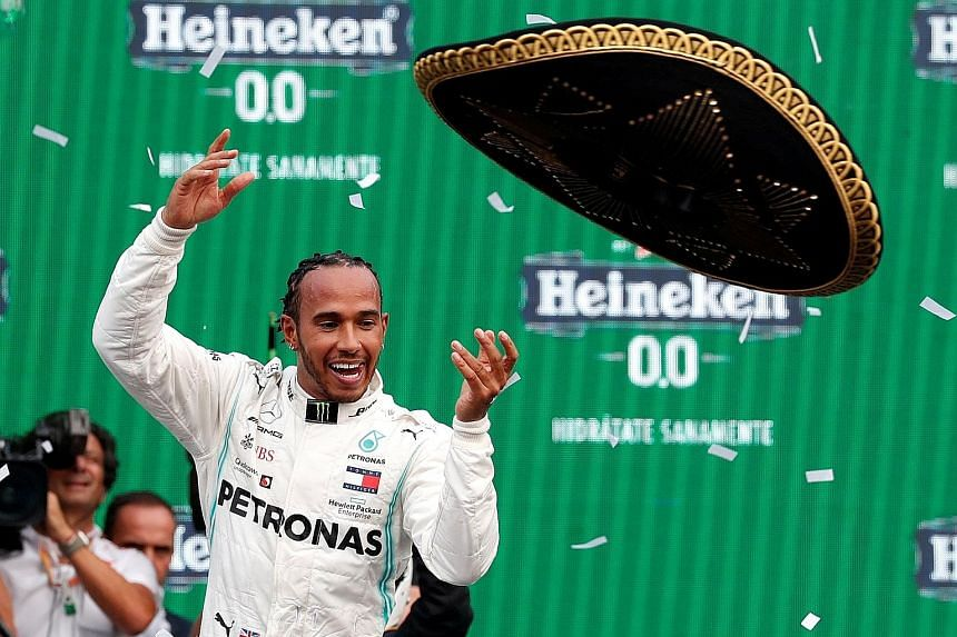 Lewis Hamilton tossing a sombrero on the podium as he celebrates winning the Mexican Grand Prix, his second victory here. He can seal the title with an eighth-place finish in Austin. PHOTO: REUTERS
