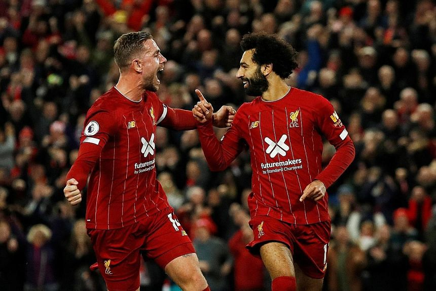 Mohamed Salah celebrating his 50th goal at Anfield with Liverpool skipper Jordan Henderson, who earlier scored the equaliser against Tottenham. The Reds won 2-1 to stay unbeaten. PHOTO: REUTERS