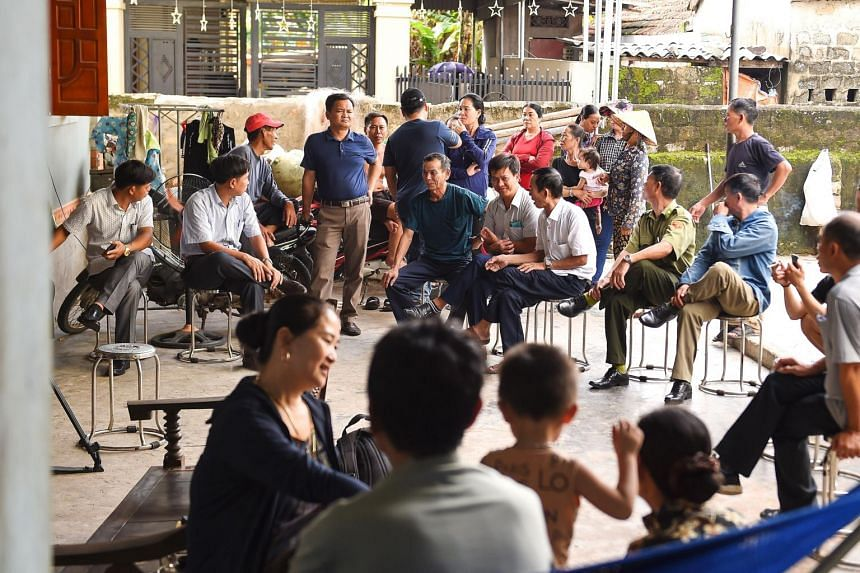 Villagers and local police personnel gather at the house of 18-year old Hoang Van Tiep who is feared to be among the 39 people found dead in a truck in Britain, in Dien Thinh commune of Vietnam's Nghe An province, on Oct 28, 2019.