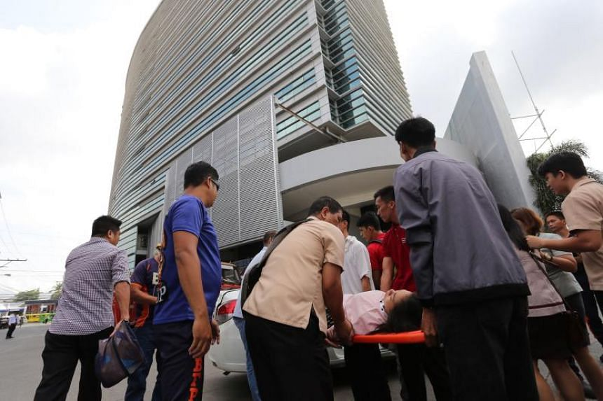 An office worker is carried on a stretcher after she fainted at the height of the earthquake that hit Davao City, on the southern island of Mindanao, on Oct 29, 2019.