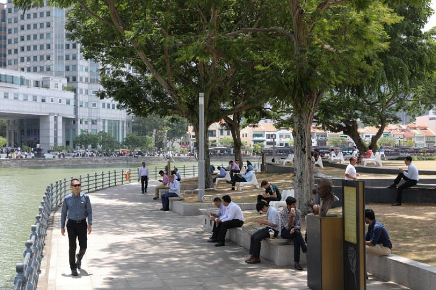 A photo taken on Oct 15 shows office workers near the Singapore River during lunch hour.