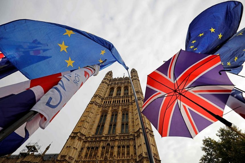 In this photo taken on Oct 23, 2019, the EU flag and Union flag-themed umbrellas fly outside the Houses of Parliament in London. The production of millions of Brexit coins was paused last week when it became clear there would be a delay.