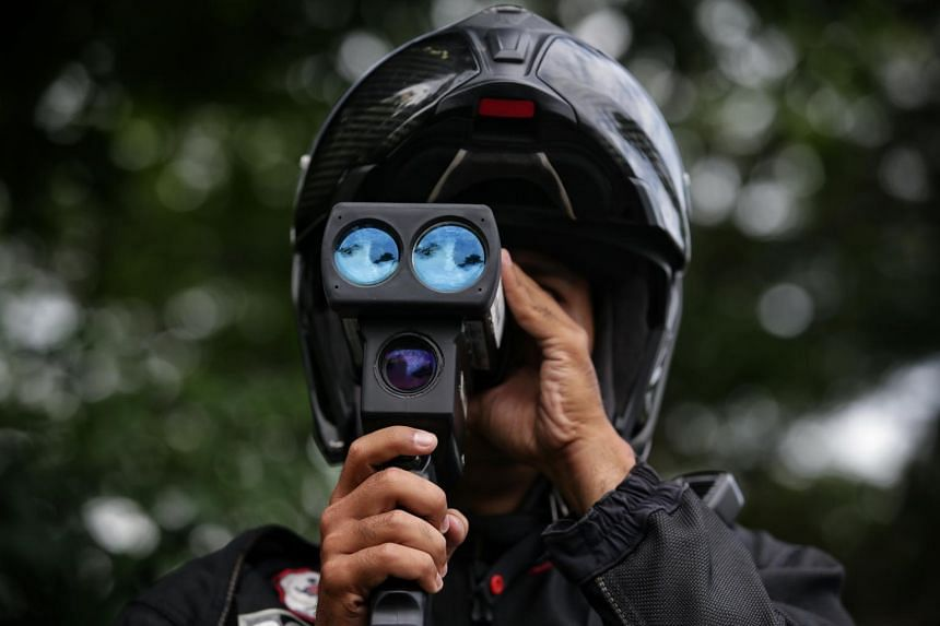 A Traffic Police Officer uses a lasercam to monitor speed on the SLE during a covert enforcement ops against errant drivers on Oct 23, 2019.