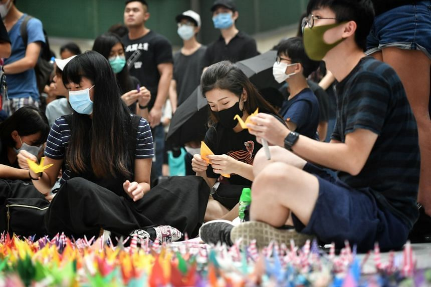 """In a photo taken on Oct 2, protesters fold paper cranes at New Town Plaza in Sha Tin to form the words """"Free HK""""."""