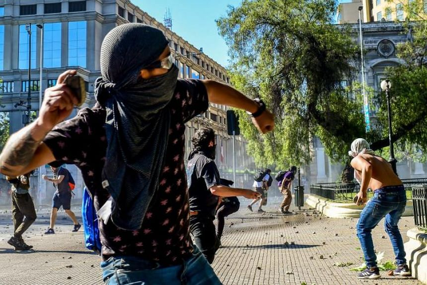 Demonstrators throw stones during clashes with the police outside La Moneda presidential palace, in Santiago, Chile, on Oct 28, 2019.