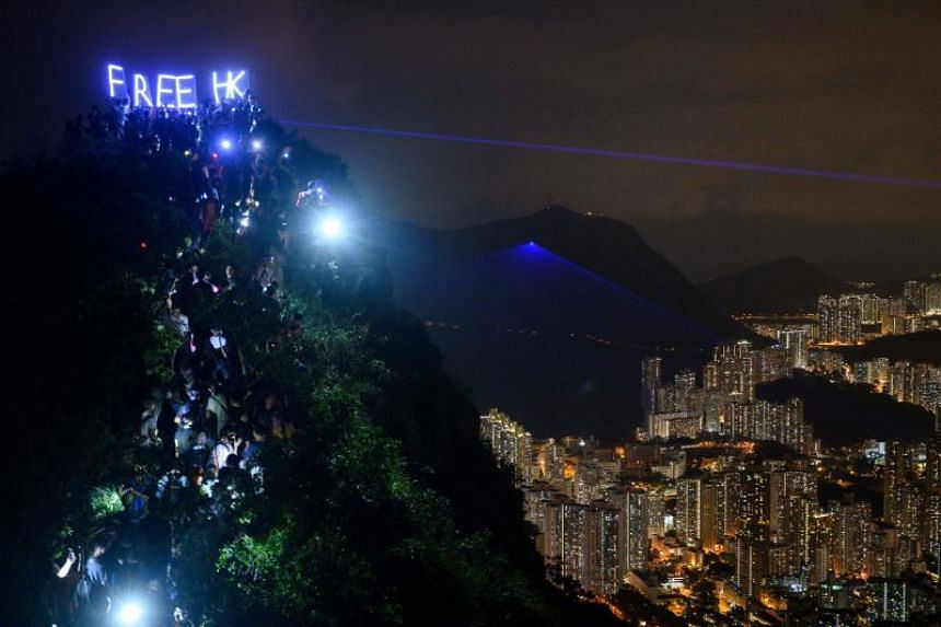 """In a photo taken on Sept 13, pro-democracy activists hold up LED lit letters which read """"Free HK"""" as others shine torch lights, lights from their phones and lasers while forming a human chain on Lion Rock in Hong Kong."""