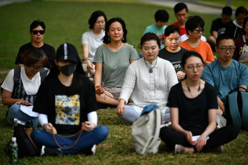 In a photo taken on June 15, an independent Buddhist group prays in a prayer meeting at Tamar Park in Hong Kong.