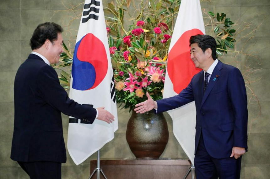 South Korean Prime Minister Lee Nak-yon (left) shakes hands with Japanese Prime Minister Shinzo Abe prior to their meeting at Abe's official residence in Tokyo on Oct 24, 2019.