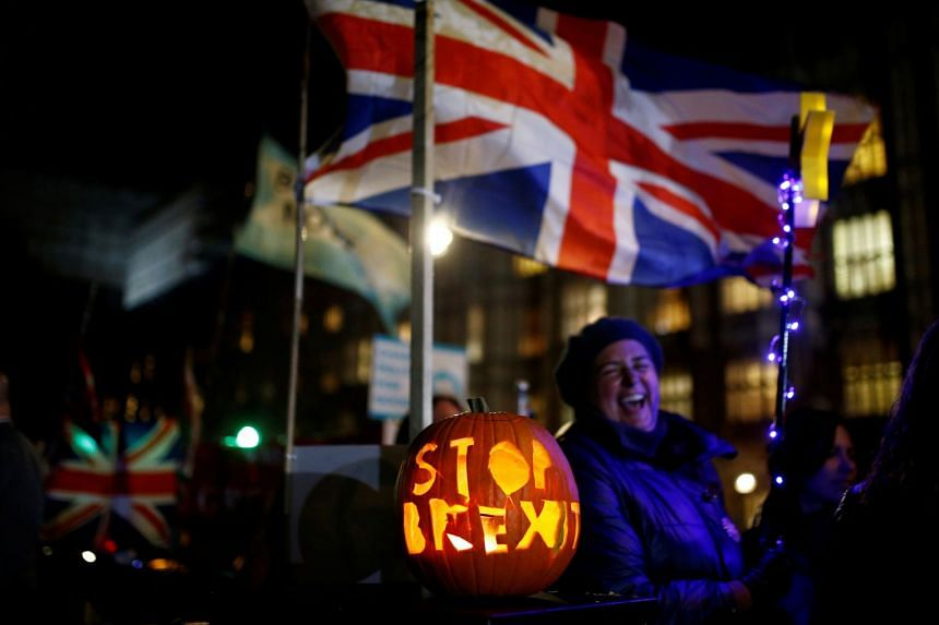 """A pumpkin with """"Stop Brexit"""" engraved on it sits outside the Houses of Parliament in London."""