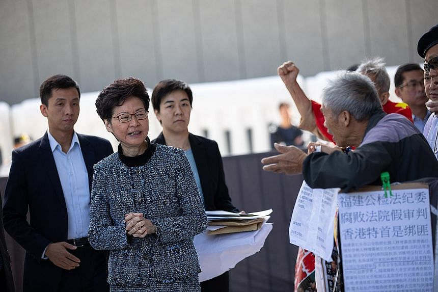 Hong Kong Chief Executive Carrie Lam receiving petition letters from citizens at the Central Government Offices in Hong Kong yesterday. PHOTO: EPA-EFE
