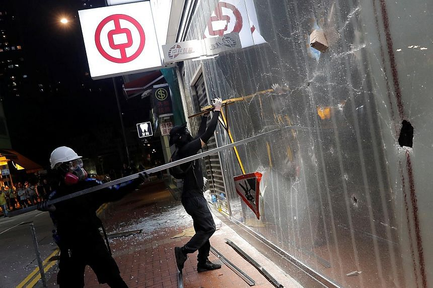 Protesters vandalising a branch of Bank of China in Tsuen Wan, Hong Kong, this month. A stress test done by JPMorgan projected that the city's lenders could see earnings fall 24 per cent to 45 per cent next year and 39 per cent to 67 per cent in 2021
