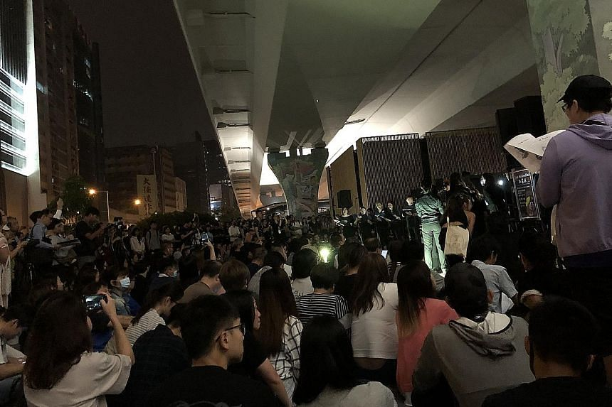 """Above: Protesters folding paper cranes at a Sha Tin mall to form the words """"Free HK"""" this month. The event was one of many community activities to maintain the momentum of the protest movement. Below: Hundreds gathering under a flyover in Kwun Tong o"""
