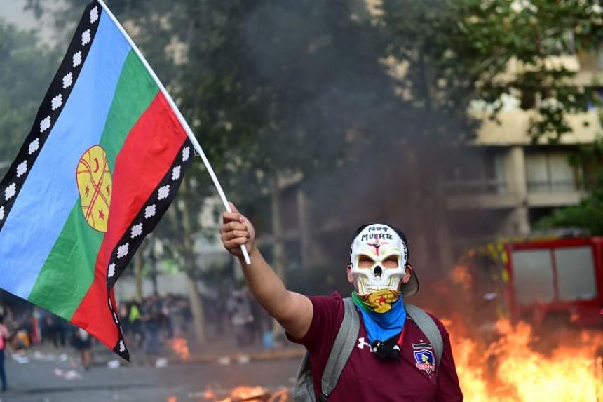 """A demonstrator with a Mapuche indigenous flag and a mask reading """"No more death"""" protests against the Chilean government's economic policies in the surroundings of La Moneda presidential palace in Santiago on Oct 29, 2019."""