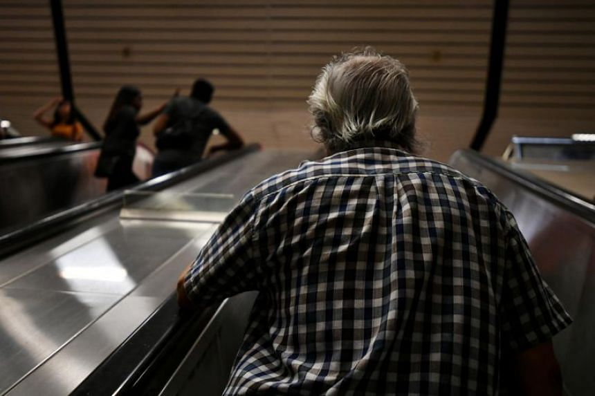 An elderly man goes up the escalator at Ang Mo Kio MRT station on Dec 13, 2018.