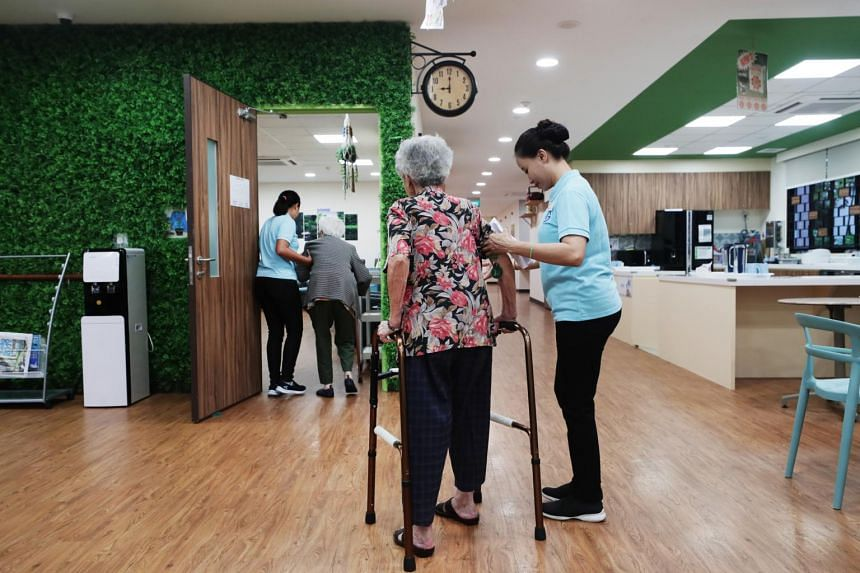 Healthcare assistants assisting the elderly at Ghim Moh Senior Care Centre.