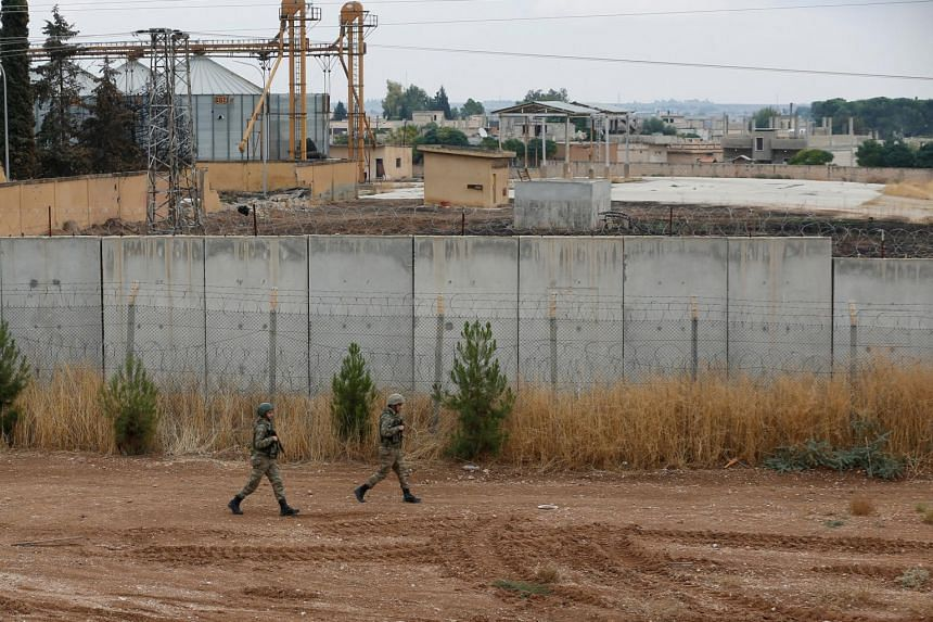 Turkish soldiers patrol along a wall on the border line between Turkey and Syria, in the Turkish border town of Ceylanpinar, in Sanliurfa province, Turkey on Oct 29, 2019.