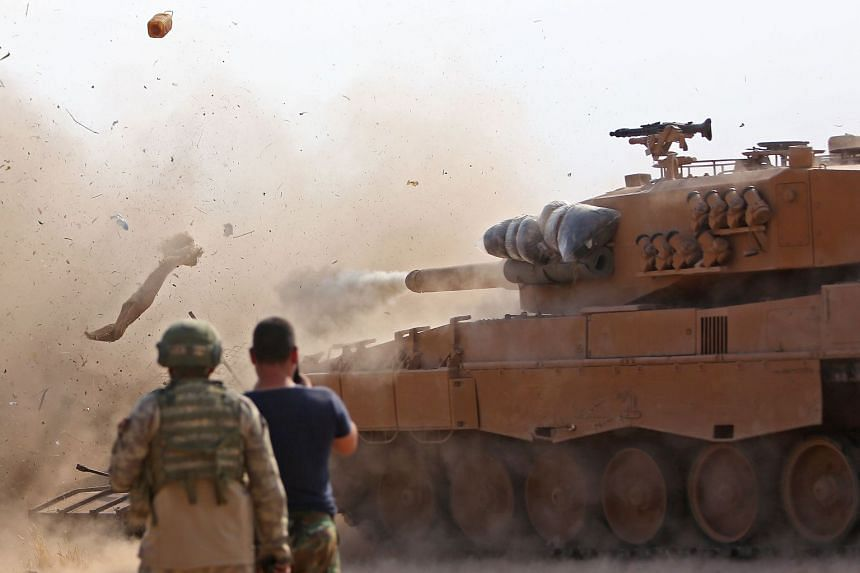 Turkish soldiers at a position east of the northeastern Syrian town of Ras al-AIn watch as a tank fires on positions held by fighters from the Syrian Democratic Army on Oct 28, 2019.