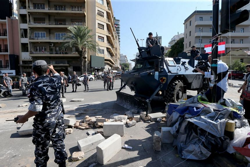Lebanese policemen patrol as anti-government protestors begin removing their tents from the main highway leading to east Beirut, Lebanon, on Oct 30, 2019.