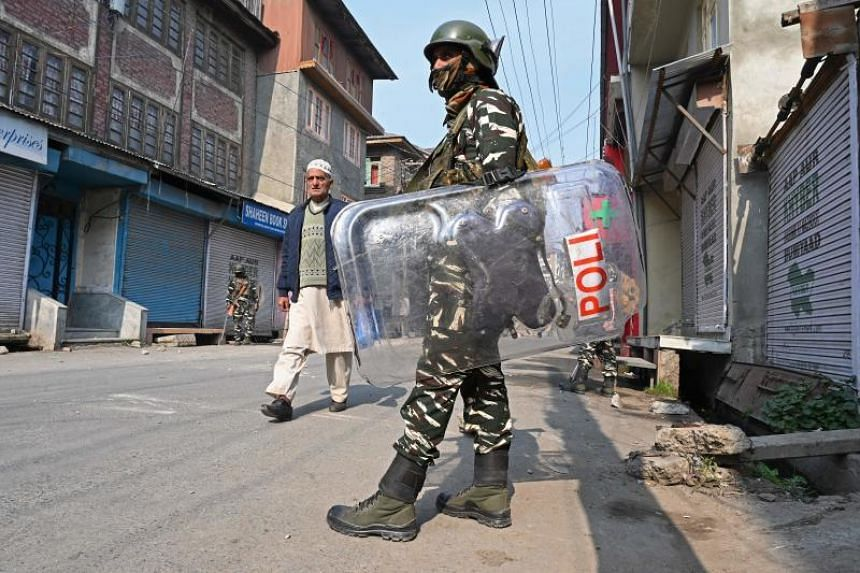 A resident walks past Indian paramilitary troopers standing guard during a lockdown in Srinagar on Oct 29, 2019.