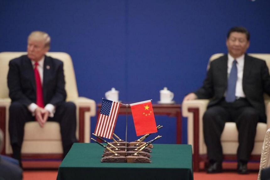 In this file photo taken on Nov 9, 2017, US President Donald Trump (left) and Chinese President Xi Jinping attend a business leaders event inside the Great Hall of the People in Beijing.