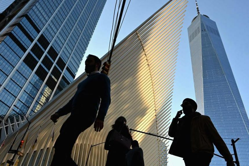 In this file photo taken on Oct 24, 2019, people walk past the Oculus and One World Trade Center in New York City.