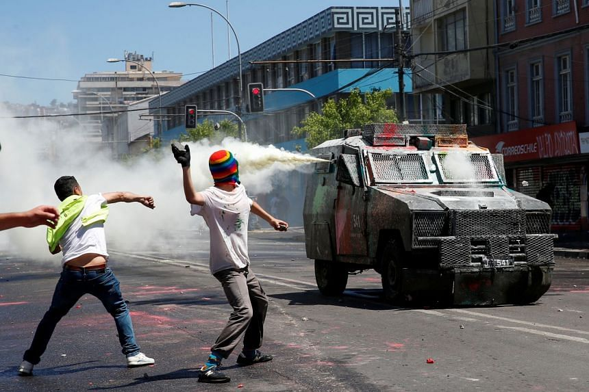 Demonstrators throw stones at a riot police vehicle during a protest against Chile's government in Valparaiso, Oct 30, 2019.