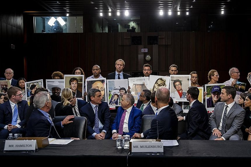 Boeing's chief executive Dennis Muilenburg looking back at family members of the 737 Max crash victims during a Senate hearing on Capitol Hill on Tuesday. He was testifying before Congress for the first time since the crashes of two 737 Max jets that
