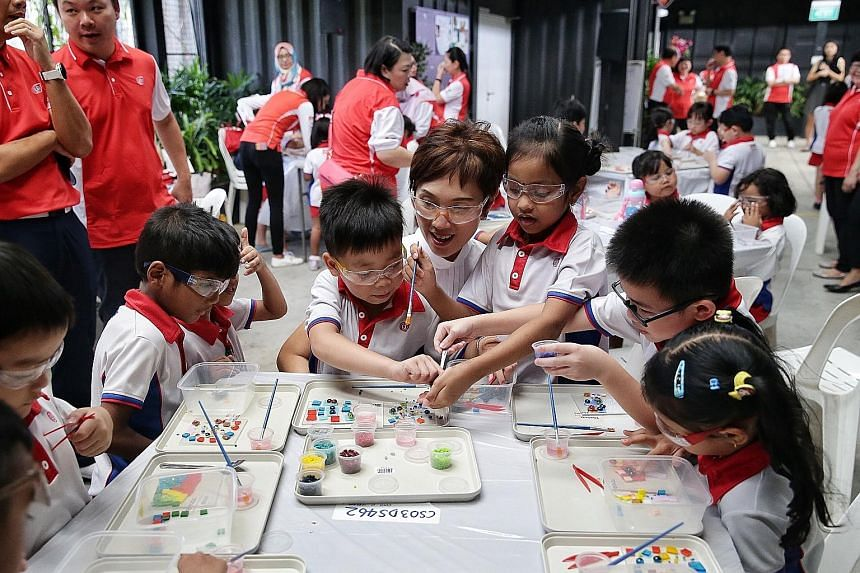 Manpower Minister Josephine Teo helping PCF Sparkletots K2 children Chang Ann Kiet and Rebecca Aarin, both six, in a glass art class at Goodman Arts Centre yesterday.